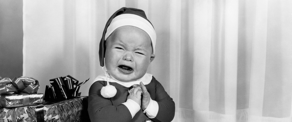 A baby cries while wearing a Santa suit and surrounded by presents