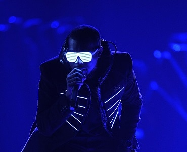Kanye West performs while wearing shutter shades