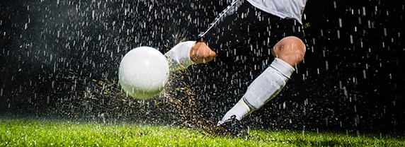 Soccer striker kicking the ball in torrential rain