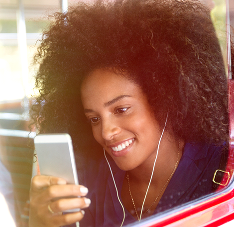 Girl with headphones streaming movies and TV on mobile phone on public transport - Optus