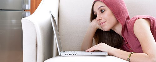 Young woman using NBN on laptop